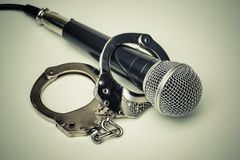 A microphone with handcuffs Stock Photo