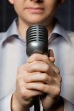 Microphone in hands of man, focus on fingers. On dark Stock Photos
