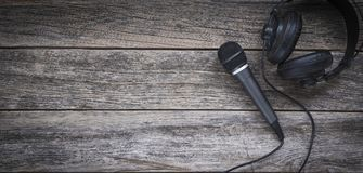 Microphone and headphone on a wooden background. With copy space Stock Photos