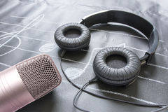 Microphone and headphones on black music note Royalty Free Stock Images