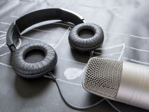 Microphone and headphones on black music note Royalty Free Stock Photos