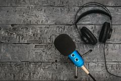 Microphone and headphones on a black wooden table. Equipment for conferences, music studios and meetings. Microphone and headphones on a black wooden table. The royalty free stock images