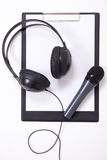 Microphone, headphones and clipboard with blank paper Stock Images