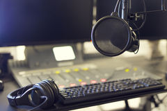 Microphone and headset in radio station broadcasting studio. Close-up of a microphone in front of a sound mixer, headset and computers in broadcasting radio Stock Photos