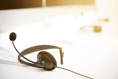 Microphone headsets on the table with computer keywords. Call center concept royalty free stock images