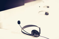 Microphone headsets on the table with computer keywords Royalty Free Stock Photo