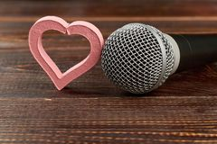Microphone and heart on wooden background.
