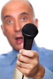 Microphone held by a surprised reporter. In the background Royalty Free Stock Photography