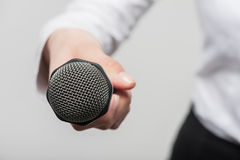 Microphone is hold by girl tv journalist Stock Photos