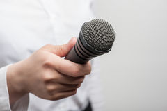 Microphone is hold by girl tv journalist Royalty Free Stock Images