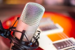 Microphone in home recording studio with red guuitar on background. Large condenser microphone in home recording studio with red guuitar on background Royalty Free Stock Photography