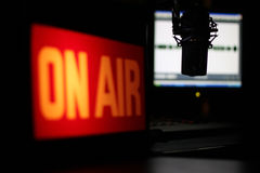 Microphone Interview. Radio studio with focus on the microphone and the interview about to unfold.  Images features illuminated On Air sign and wave form monitor Stock Photo