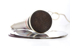 The microphone lays on  compact discs. On  white background Royalty Free Stock Image