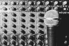 The microphone lies on the mixer. The microphone rests on an audio mixer Royalty Free Stock Photo