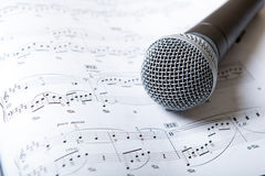 Microphone lies on the music book. Close up Stock Images