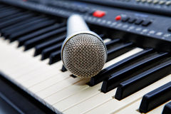 The microphone lies on the synthesizer Stock Image