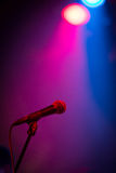 Microphone in Lights. A band stage microphone on a stand highlighted by a pink and blue light Royalty Free Stock Images