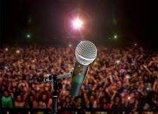 Microphone Live in Concert with Spotlights. And People Waving hands Royalty Free Stock Images