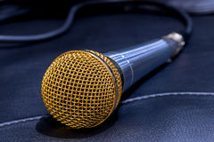 Microphone lying on a black leather couch Stock Image