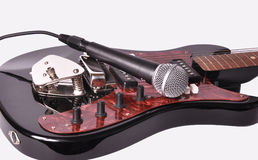A microphone lying on a guitar Royalty Free Stock Photos