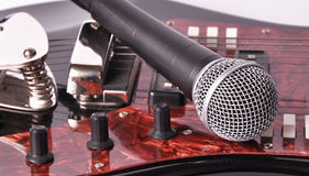A microphone lying on a guitar Stock Photography