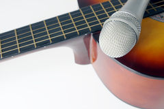 Microphone lying on a guitar Stock Photos