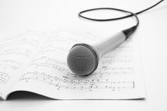 Microphone lying on the musical book. Close-up Stock Photos