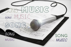 Microphone lying on the musical book. Close-up Royalty Free Stock Photos