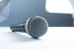 A microphone lying on a white table. Against the background of studio equipment, lighting stock image