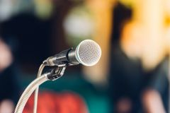 Microphone in meeting room use for amplify talk. Microphone in seminar event or meeting room use mic for sound amplify when talk or communicate on stage defocus stock image
