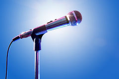 Microphone on microphone stand with blue background Stock Photos