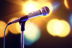 Microphone on microphone stand with lights in the background Stock Photos