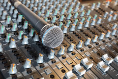 Microphone on a mixing desk. Microphone resting on a sound console in a recording studio Royalty Free Stock Photos