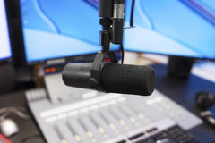 Microphone in modern radio station broadcasting studio. Microphone in front of the sound mixer and computers in broadcasting radio studio. New radio station Stock Photography