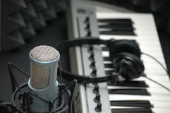Microphone at Music Studio. With keyboard and earphones by sound panels Stock Photos