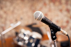 Microphone in music studio. Stage with out of focus drums in background Royalty Free Stock Photo