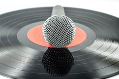 Microphone on old disc. Isolated on white background - music concept Royalty Free Stock Photography