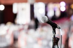 Microphone over the Abstract blurred photo of banquet room or seminar room with people background,party or meeting. Concept royalty free stock images