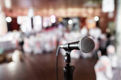 Microphone over the Abstract blurred photo of banquet room or seminar room with people background,party or meeting. Concept stock photography