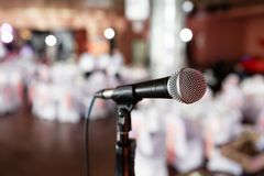 Microphone over the Abstract blurred photo of banquet room or seminar room with people background,party or meeting. Concept stock images