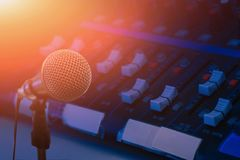 Microphone over the abstract blurred photo of conference hall or seminar room background, Dark background stock photos