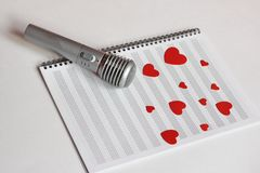 Microphone and paper red hearts are located on a clean music notebook. The concept of music and love. Valentine`s day royalty free stock images
