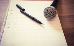 Microphone and paper. Microphone on a wooden background royalty free stock photography