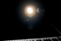 Microphone and piano in dark background Stock Photos