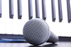 Microphone and piano keyboard on black table Royalty Free Stock Photo