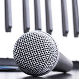 Microphone and piano keyboard on black table Royalty Free Stock Photos