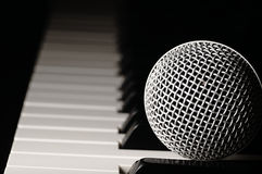 Microphone on a piano keyboard. stock image