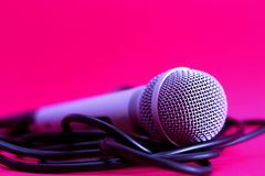 Microphone on pink. Close up of professional silver microphone with wire on pink background Stock Photo