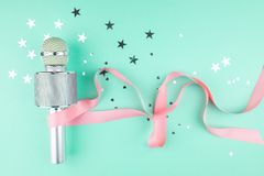 Microphone with a pink ribbon on a green background with confetti. Homemade karaoke stock images