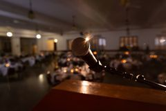 Microphone at podium in front of empty auditorium. View of microphone from podium on stage facing empty auditorium royalty free stock photography